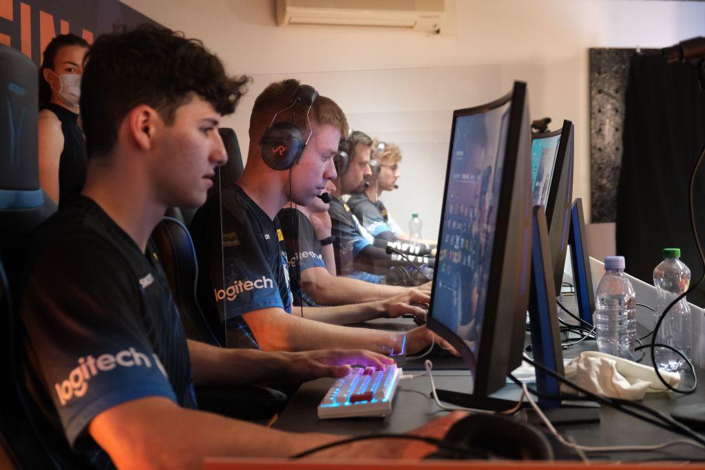 Man sieht fünf Spieler an einem Esports Finale gegeneinander Spielen.
